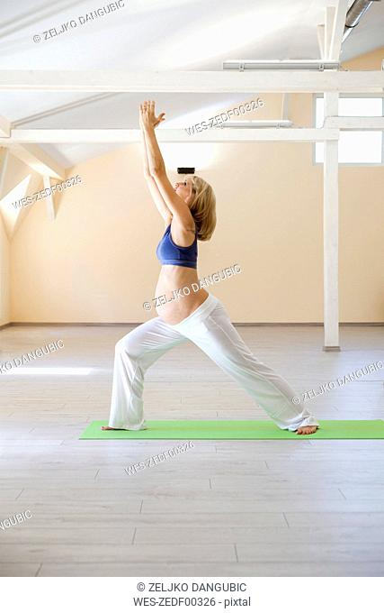Prenatal yoga, woman doing warrior asana