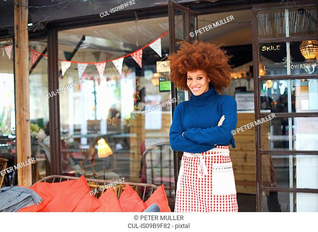 Portrait of small business owner in front of cafe looking at camera smiling