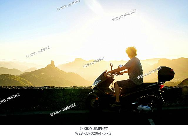 Spain, Canary Islands, Gran Canaria, man on motor scooter watching sunset over mountainscape