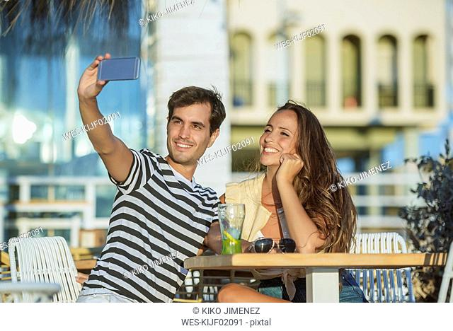 Happy young couple taking a selfie on the terrace of a bar