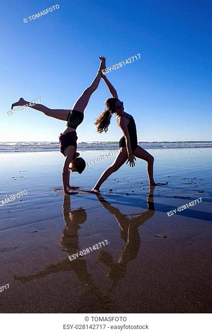 two girls doing yoga on the beach