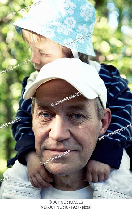 Portrait of man carrying grandson on shoulders