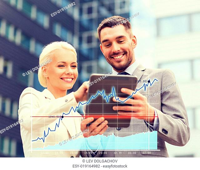business, partnership, technology and people concept - smiling businessman and businesswoman with tablet pc computer over office building background