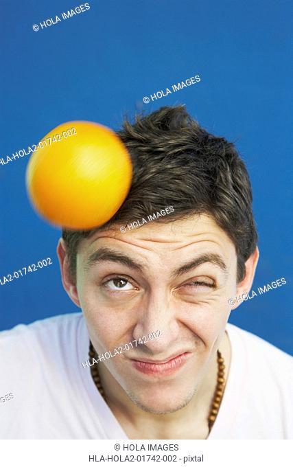 Young man balancing an orange on his head