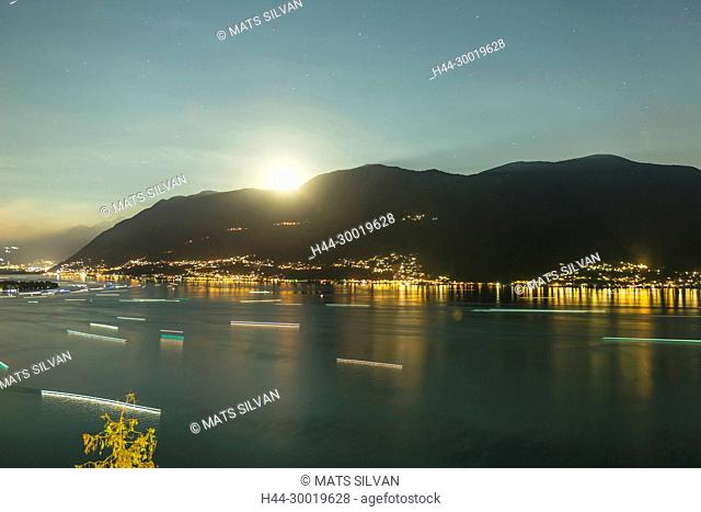 Alpine Lake maggiore with Mountain and Boats in Long Exposure and Moolight in Ticino, Switzerland