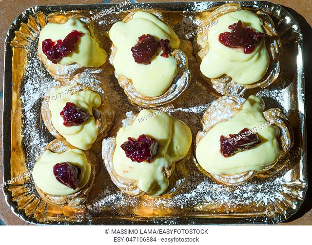 Zeppole of Saint Joseph, Italian pastry with flour, sugar, eggs, oil, decorated with a sour cherry. Father's Day cake
