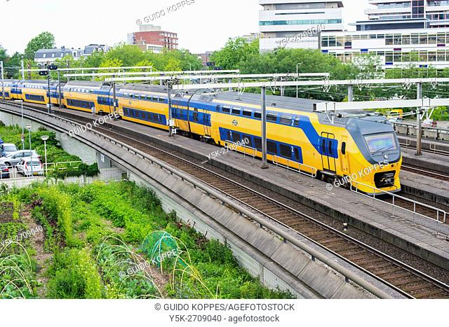 Rotterdam, Netherlands. Yellow and blue colored Dutch Intercity train entering a down town track tunnel after departing from Rotterdam Grand Central Station
