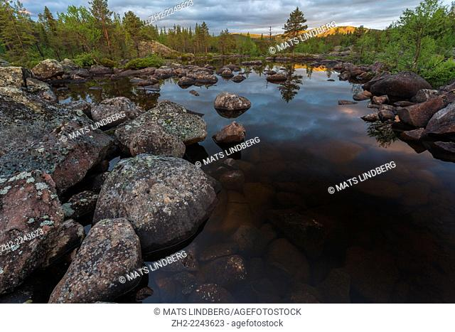 Landscape over small lake in forest with sky reflection and rocks sticking upp in the lake, Kvikkjokk, Swedish lapland