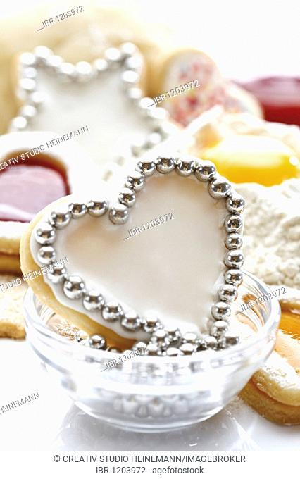 Heart-shaped short pastry cookies, covered with sugar icing and silver pearls