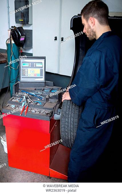 Mechanic prepares a tyre balance machine