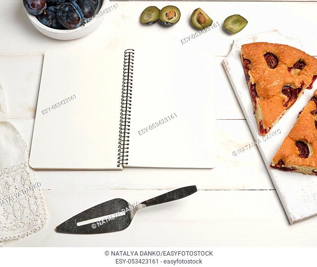open notebook with blank white pages, baked pie with plums and fresh fruits, top view, flat lay