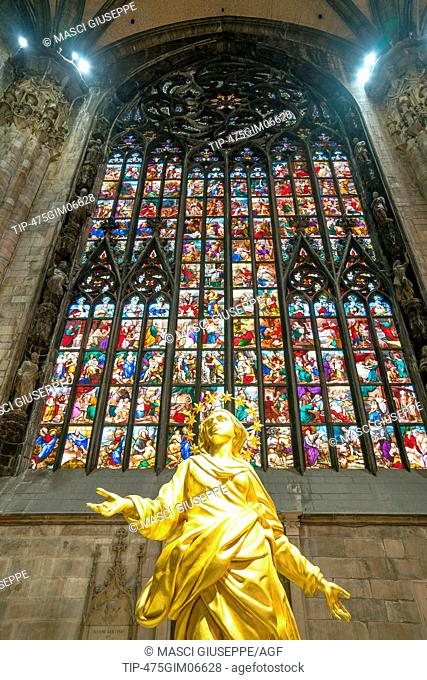 Milan, Italy, The interior of the Duomo Cathedral, the colorful stained glass of the apse with the golden statue of the Madonna in the foreground
