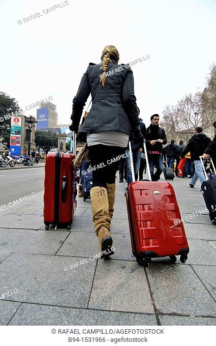 Girl walking with trolleys. Catalunya square. Barcelona. Catalonia. Spain