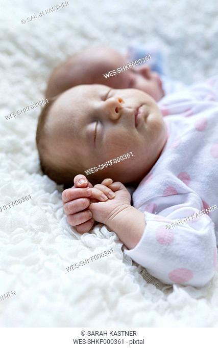 Portrait of sleeping newborn baby girl lying besides her twin brother
