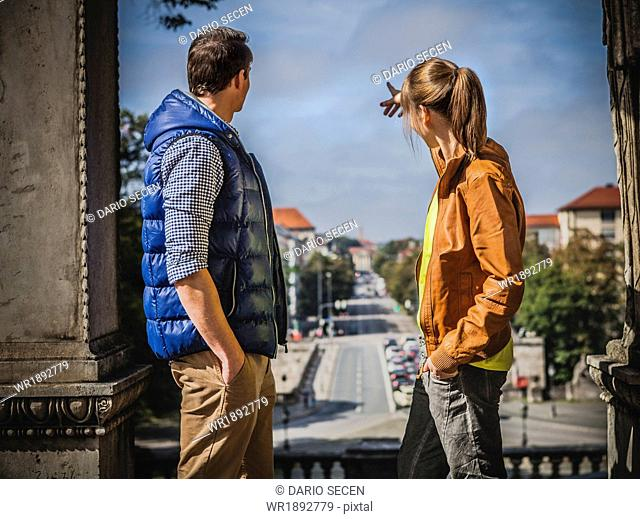 Young couple overlooking town, Munich, Bavaria, Germany