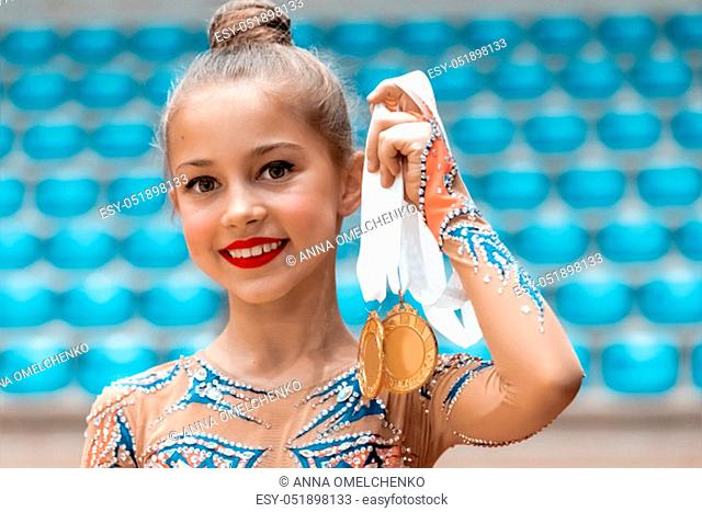 Little champion, portrait of a happy girl who won a gold medal in rhythmic gymnastics competition, great accomplishment in the kids sports