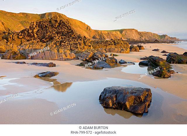 Golden evening light illuminates a deserted Sandymouth Bay in North Cornwall, England, United Kingdom, Europe