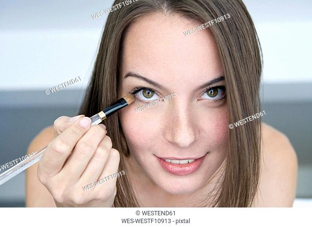 Young woman applying eye shadow, portrait,, close-up
