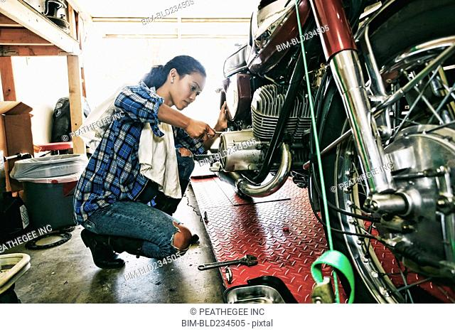 Mixed Race woman repairing motorcycle in garage