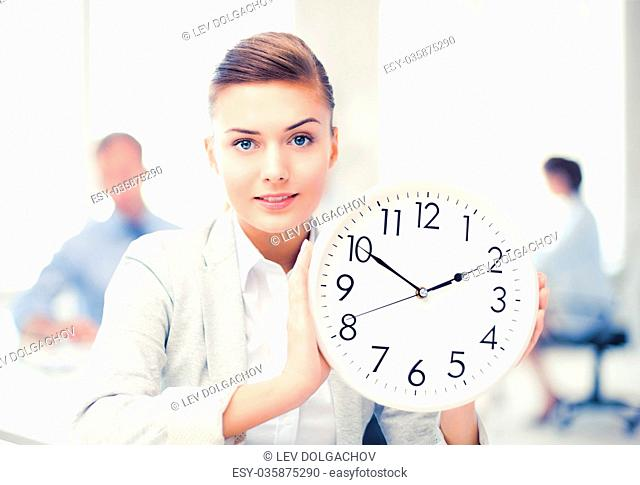 businesswoman showing white clock in office