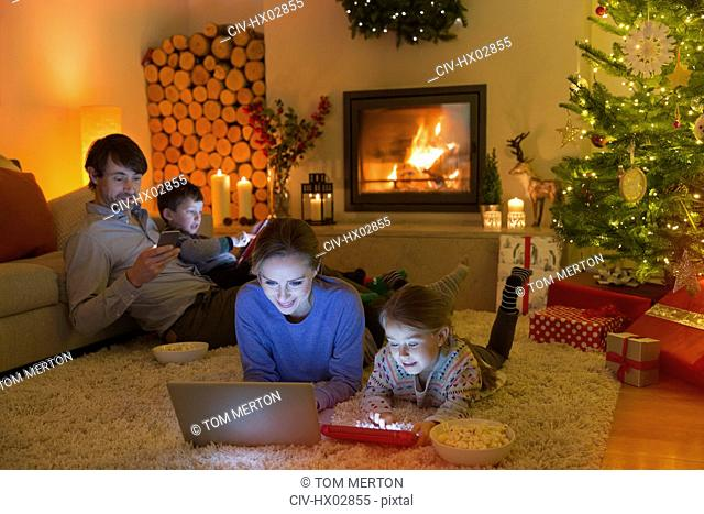 Family relaxing, using laptop, digital tablet and cell phone in ambient Christmas living room