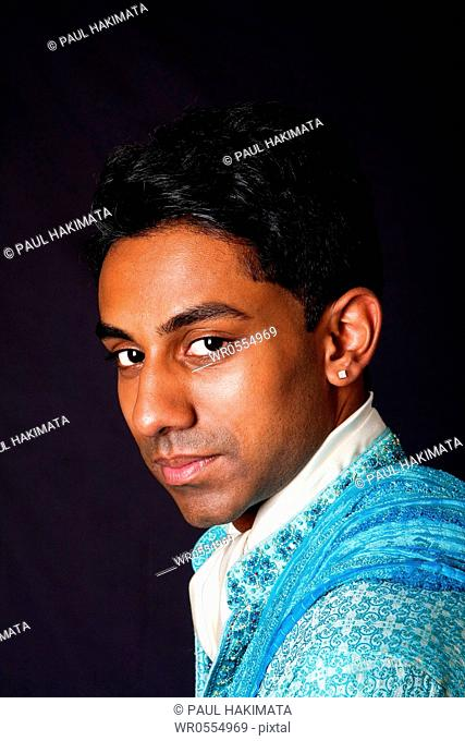 Beautiful face of an Indian Hindu young man with earring wearing blue Dhoti. Portrait of handsome Desi male, isolated