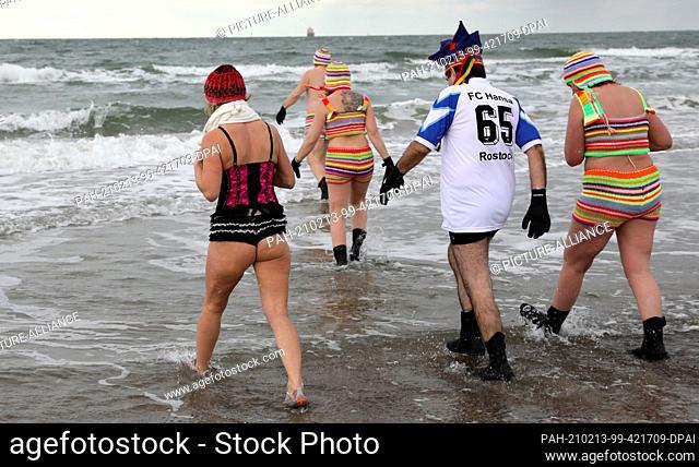 11 February 2021, Mecklenburg-Western Pomerania, Warnemünde: Members of the Rostocker Seehunde e.V. club take to the 1.5 degree cold Baltic Sea
