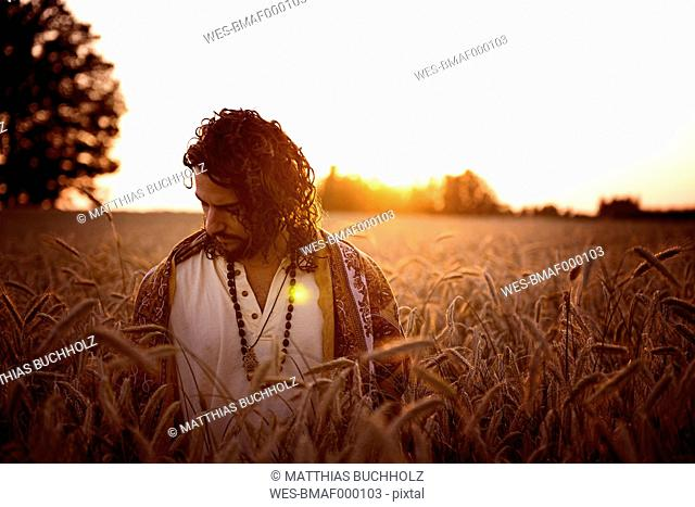 Man standing in corn field looking down