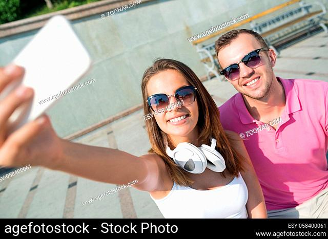 Young smiling couple in summer street taking selfie portrait