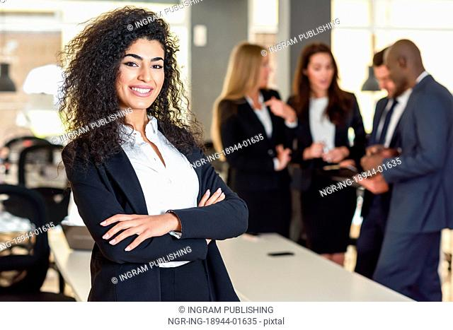 Businesswoman leader looking at camera in modern office with businesspeople working at the background. Teamwork concept. Muslim woman