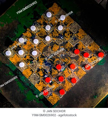 Plastic bottle caps (checkers pieces) are seen positioned before the game begins on an outdoor checkerboard table in the park in San Salvador, El Salvador