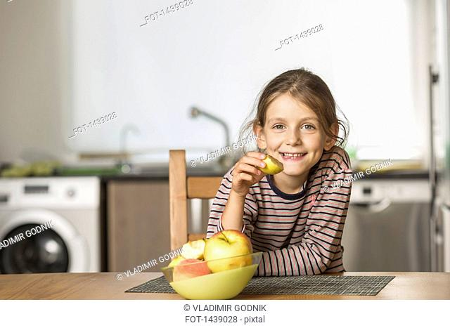 Portrait of happy girl eating apple at table