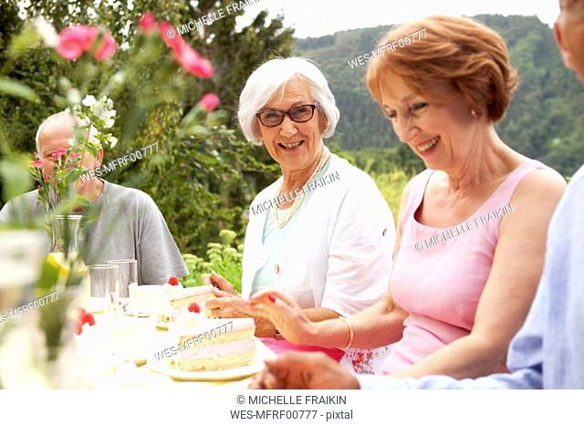 Senior ladies eating cake in garden