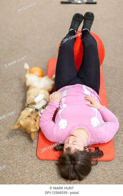 Girl with Down Syndrome working out on a yoga mat with her dog