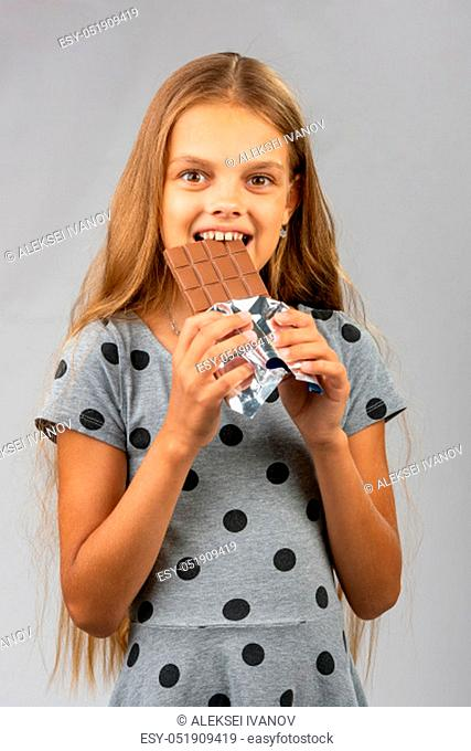Ten-year girl bites chocolate and happily looks into the frame