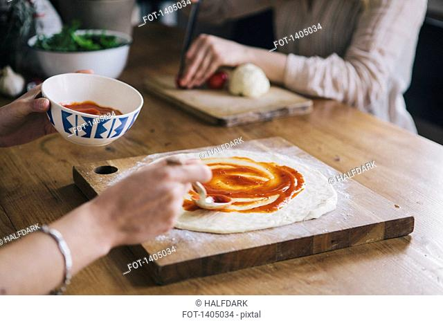 Cropped image of woman spreading tomato sauce over pizza dough