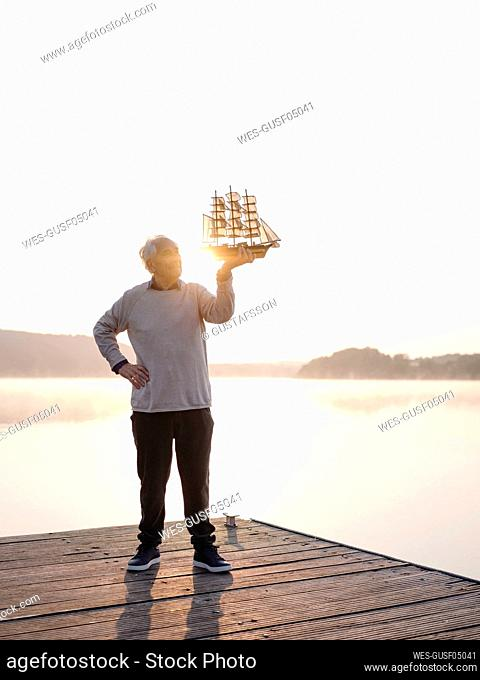 Senior man holding sailing ship while standing with hand on hip against lake