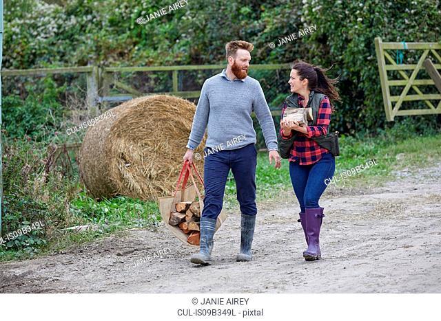 Couple on farmland carrying logs