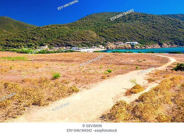 People enjoying the sunny weather on sandy Grand Capo beach with red rocks near Ajaccio, Corsica, Europe
