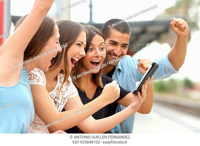 Four euphoric multi ethnic caucasian and arab friends watching tv on a a tablet in a train station