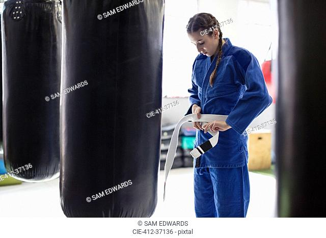 Young woman tying judo belt at punching bags in gym