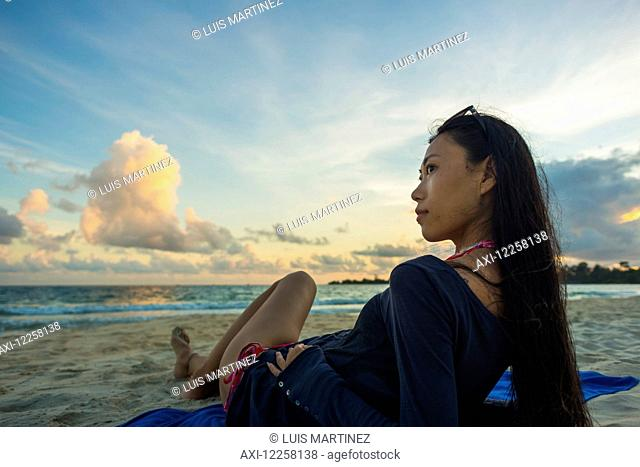 A young woman lays posing on Sokha Beach at sunset; Sihanoukville, Cambodia