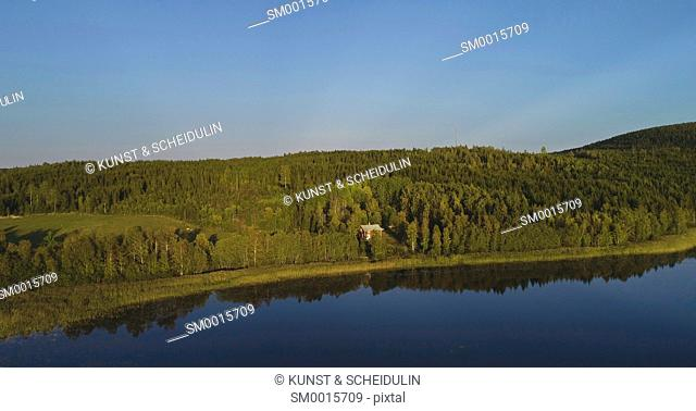 Aerial shot of a single red wooden house surrounded by forest at the shore of a glassy lake on a sunny autumn afternoon. High Coast (Höga Kusten)