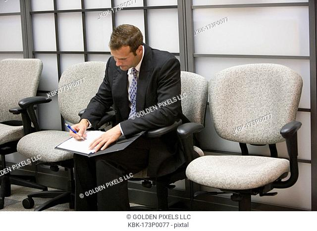 Businessman seated in an office writing in his folder