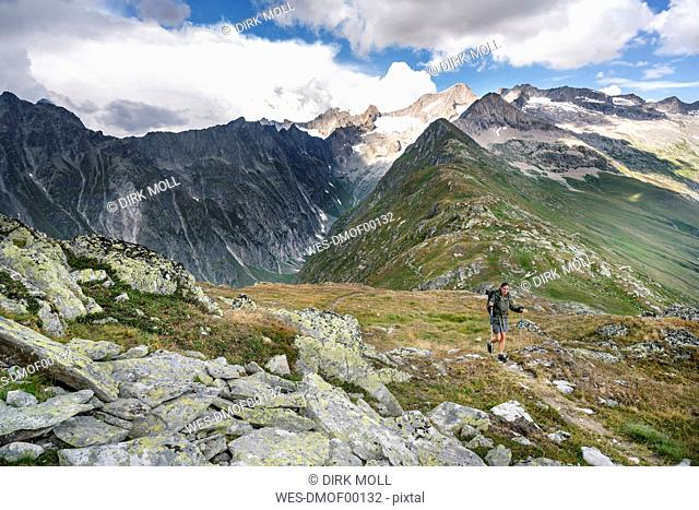 Switzerland, Valais, woman on a hiking trip in the mountains towards Foggenhorn