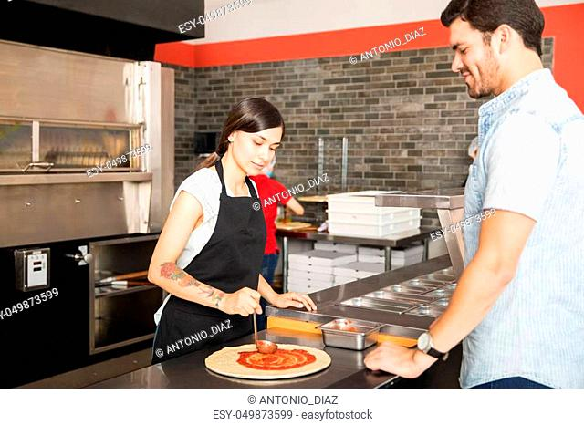 Woman chef wearing apron applying tomato sauce over dough pizza bread while customer looking at pizza
