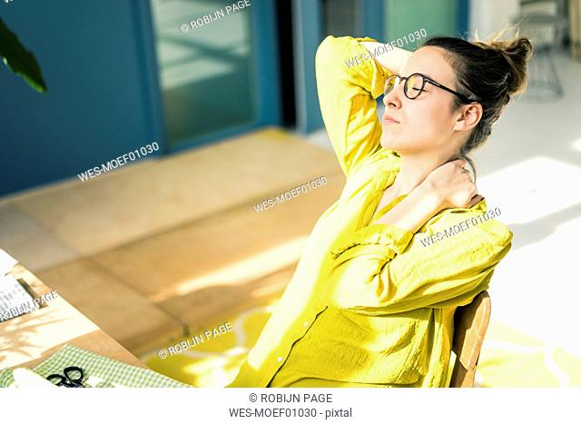 Young fashion designer relaxing at desk in her studio