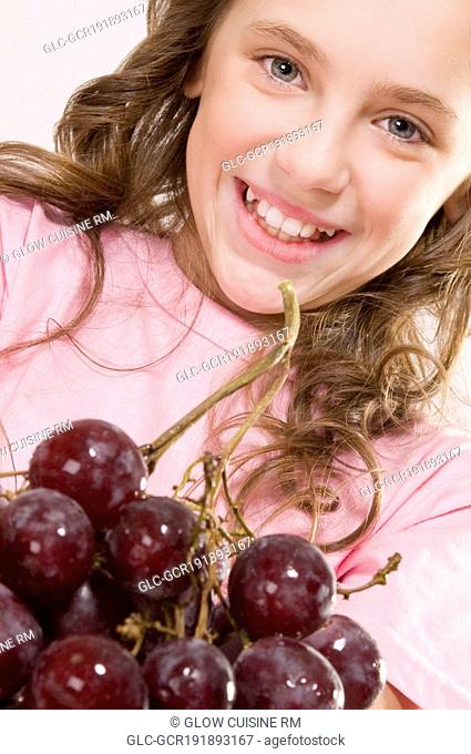 Portrait of a girl with a bunch of grapes