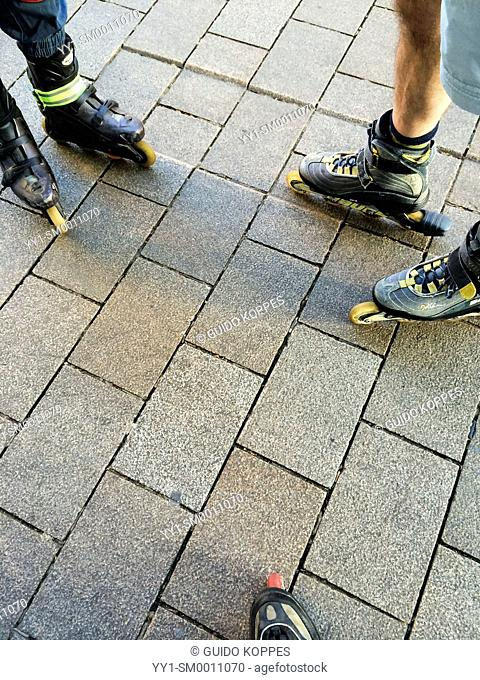 Tilburg, Netherlands. Three pair of feet in skates, prior to a Tilburg's weekly Friday Night Skate tour