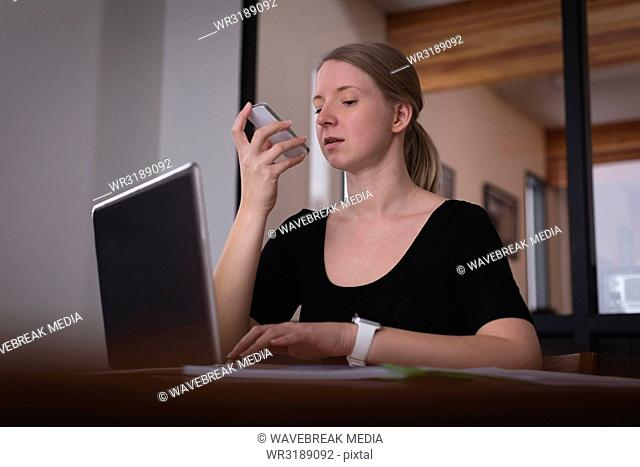 Female executive talking on mobile phone while working on laptop